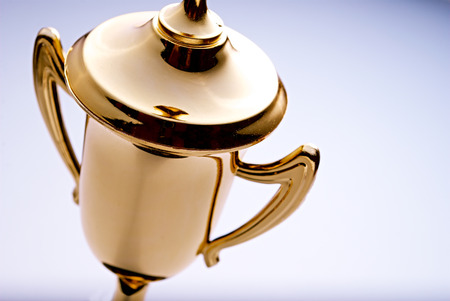 Close up high angle view of a shiny gold trophy award to be awarded to the winner or champion in a competition, with copyspace to the right Banque d'images
