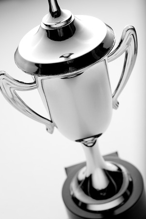 accolade: Silver trophy cup, high angle view over a grey background, to be awarded to the winner or second placed contestant in a competition or championship