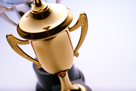 Close up high angle view of a shiny gold trophy award to be awarded to the winner or champion in a competition, with copyspace to the right Foto de archivo