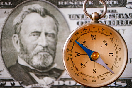 emphasizing: Conceptual Vintage Compass Instrument Standing in Front of a 50 US Dollar Bill, Emphasizing the Portrait of Ulysses S. Grant, Captured in Close up Stock Photo