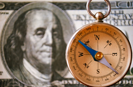 emphasizing: Conceptual Vintage Compass Instrument Standing In Front of a 100 US Dollar Bill, Emphasizing the Portrait of Benjamin Franklin, Captured in Close up.