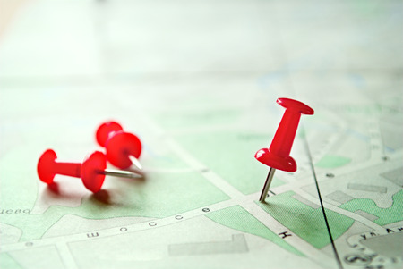 Conceptual Three Red Marking Pins on Standing and Lying on Top of a Green White Map.