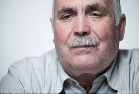 Thoughtful senior man with a moustache sitting reminiscing staring the with a serious contemplative expression Stock Photo