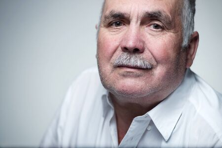 dignity: Close-up portrait of a Caucasian senior man with mustache wearing a white shirt while smiling at camera