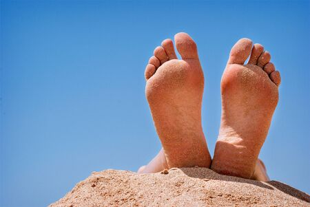 foots: Human foots close-up relaxing on the beach against the blue sky