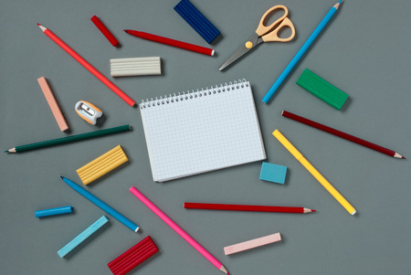 writing implements: View from above of an open blank notebook surrounded with scattered assorted stationery supplies and writing implements on a grey background Stock Photo