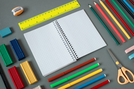 writing implements: High Angle View of Colorful School Supplies Organized by Type Around Note Book Open to Blank Page Arranged on Grey Desk