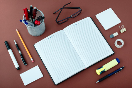 desk tidy: High Angle View of Office or School Supplies Arranged Neatly Around Notebook Open to Blank Page on Wooden Desk Surface Stock Photo