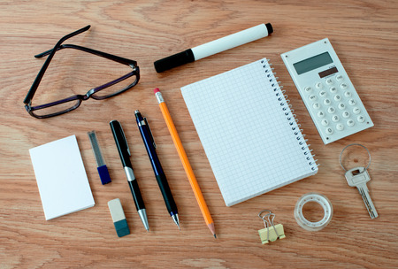 writing implements: High Angle View of Office or School Supplies Arranged Neatly Around Notebook with Blank Page on Wooden Desk Surface Stock Photo
