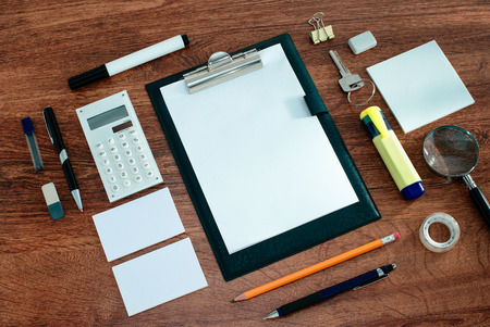 neatly: High Angle View of Office or School Supplies Arranged Neatly Around Clipboard with Blank Page on Wooden Desk Surface Stock Photo