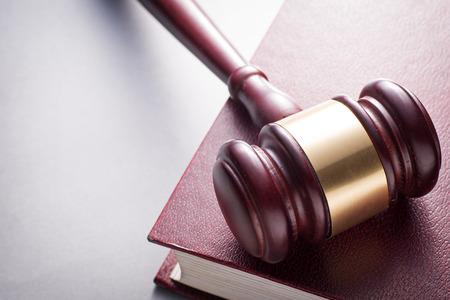 orden judicial: Ángulo de visión de alta de madera de cerezo Mazo con Brass Band de descanso en el libro encuadernado en cuero rojo en la Justicia la imagen de concepto con espacio de copia