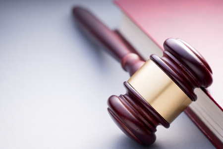 adjournment: High Angle View of Cherry Wood Gavel with Brass Band Resting on Book Bound in Red Leather in Justice Concept Image with Copy Space Stock Photo