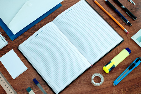 top down: High Angle View of Office or School Supplies Arranged Neatly Around Notebook Open to Blank Page on Wooden Desk Surface Stock Photo