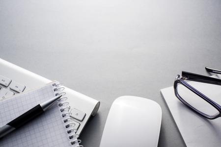 papeles oficina: Opini�n de alto �ngulo del teclado y el rat�n del ordenador Mac en gris escritorio con el cuaderno, lentes y la pluma y un amplio espacio de copia