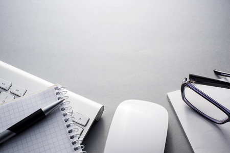 High Angle View of Mac Computer Keyboard and Mouse on Grey Desk with Note Book, Eyeglasses and Pen and Ample Copy Space Banque d'images