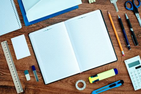 Hoog standpunt van Office of School Supplies Netjes georganiseerd rond Open Note Book met blanco pagina op Houten Desk Top