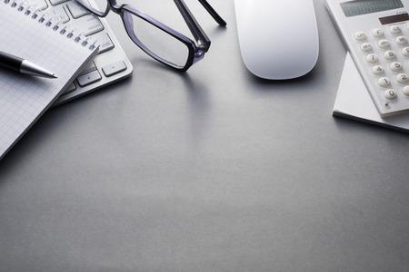 Seitlicher Blick auf Mac Computer-Tastatur und Maus mit verschiedenen Bürobedarf auf Grau für Ausflüge mit reichlich Kopie, Raum