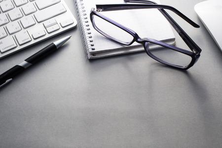 Voir coudée du clavier et de la souris d'ordinateur Mac avec divers Fournitures de bureau sur Gris bureau avec Espace texte Ample