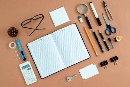 Assortment of Office Supplies Neatly Organized Around Note Book Open to Blank Page on Desk Top Surface Foto de archivo