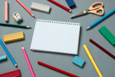writing implements: High Angle View of Colorful School Supplies Scattered Around Note Book Open to Blank Page on Grey Desk