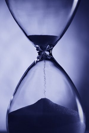 the passing of time: Hourglass in blue light closeup. For illustrations of passing time. Stock Photo