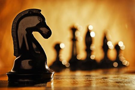Schaakridder schaakstukken aan de voorkant en op de achtergrond. Het idee van het winnen en strategieën.