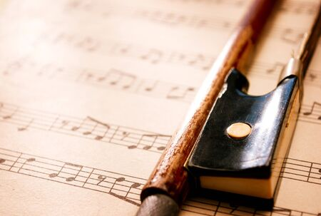 musical score: Close Up Still Life of Violin Bow Resting on Top of Sheet Music Composition, Selective Focus with Copy Space