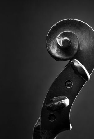 dimly: Black and White Close Up Image of Carved Scroll and Pegbox of Violin with Copy Space in Dimly Lit Studio Stock Photo
