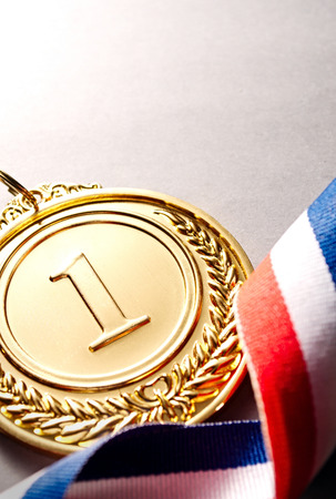 medalist: Gold medal in the foreground on three-colour ribbon