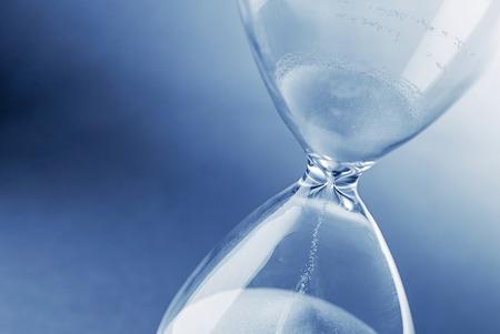 Closeup hourglass clock on light blue background Banco de Imagens