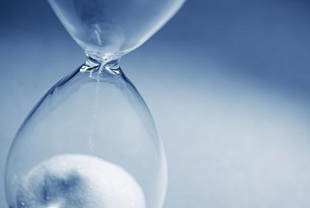 Closeup hourglass clock on light blue background 스톡 콘텐츠