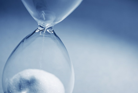 patience: Closeup hourglass clock on light blue background Stock Photo
