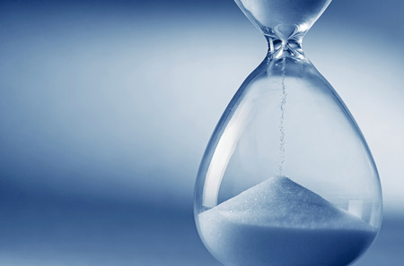 Closeup hourglass clock on light blue background Foto de archivo
