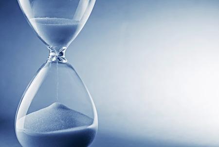 paciencia: Reloj reloj de arena de cerca sobre fondo azul claro