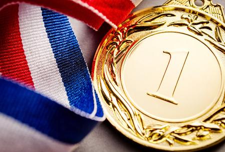 Gouden medaille op de voorgrond op drie kleuren lint Stockfoto