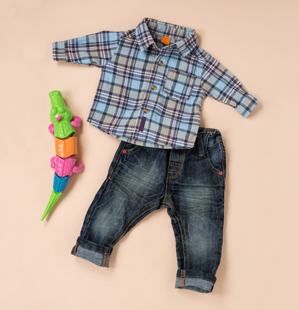worn jeans: Casual checkered shirt and blue worn jeans near a colorful toy for little boys, with copy space on beige
