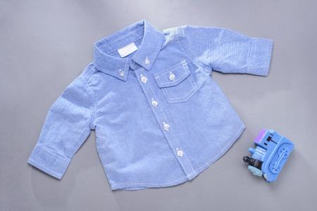 long sleeve shirt: Single blue infant buttoned long sleeve shirt with front pocket next to plastic toy train locomotive on gray background