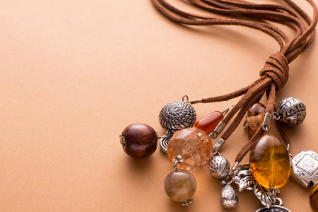 charms: High Angle Still Life View of Handmade Artisan Jewellery on Tan Background with Copy Space - Stylish and Funky Necklace Made with Brown Leather and Adorned with Silver Charms, Wood Beads and Stones