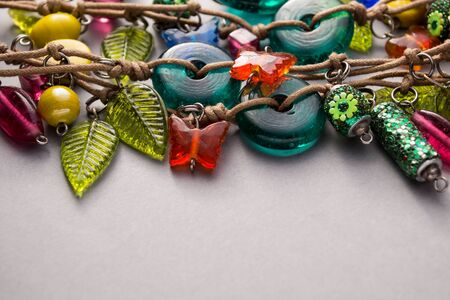 Close up of a selection of glass beads and charms on leather string against a gray background