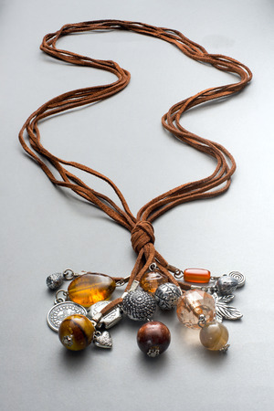 string together: Several silver and glass beads attached to brown leather string and knotted together on gray background Stock Photo