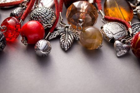 charms: Close up of silver charms and glass beads attached to red leather string on grey background