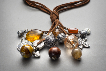 bunched: Close up of silver and glass beaded necklaces on brown leather string bunched together Stock Photo