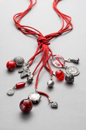 bunched: Several glass and silver beads attached to red leather string and bunched together