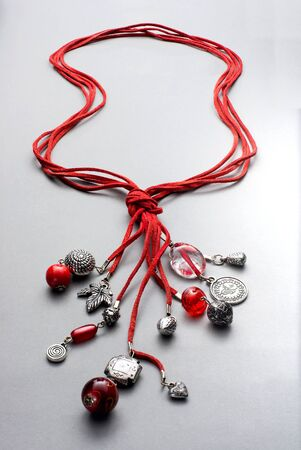 bunched: Bunched necklaces made of red glass beads and silver charms attached to red leather string