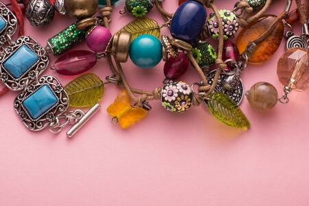 fashion style: High Angle Still Life Close Up View of Handmade Artisan Jewellery on Pink Background with Copy Space - Fashionable and Intricate Bracelets and Necklaces with Colorful Beads, Stones and Baubles