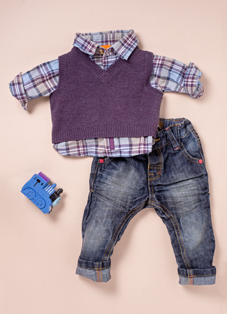 cuffed: Infant size blue and purple flannel shirt, knit sweater and rolled up cuffed blue jeans with blue plastic toy train