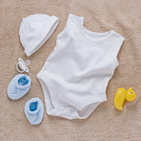 ducky: Single sleeveless onsie, little hat, blue sock boots, pacifier and rubber ducky over brown towel or carpet Stock Photo