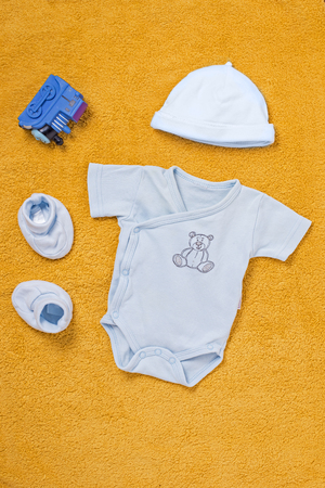 undergarment: Little blue baby sleep suit with white cap, plush booty shoes and toy plastic train over yellow soft background Stock Photo