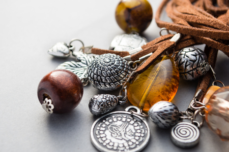 fashion style: Close up of metal charms and wood beads attached to brown leather on gray background