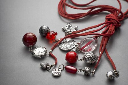 tied together: Various red stringed necklaces tied together with beads and trinkets over gray background